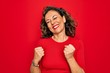 Middle age senior brunette woman wearing casual t-shirt standing over red background excited for success with arms raised and eyes closed celebrating victory smiling. Winner concept.