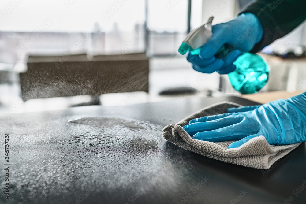 Fototapeta Sanitizing surfaces cleaning home kitchen table with disinfectant spray bottle washing surface with towel and gloves. COVID-19 prevention sanitizing inside.
