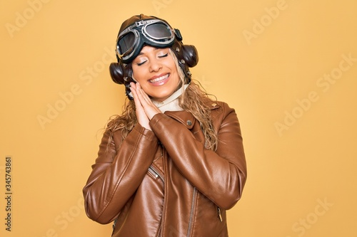 Fototapeta Young beautiful blonde aviator woman wearing vintage pilot helmet whit glasses and jacket sleeping tired dreaming and posing with hands together while smiling with closed eyes