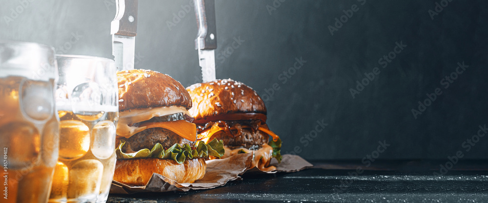 Fototapeta two delicious beef burger on a wooden table near two glass of cold beer