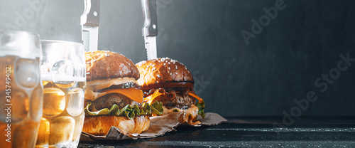 two delicious beef burger on a wooden table near two glass of cold beer Canvas Print
