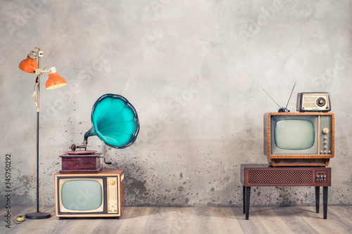 Retro analog CRT televisions, wooden TV stand with outdated amplifier, old radio receiver from 60s, classic gramophone, floor lamp front aged concrete wall background Canvas Print