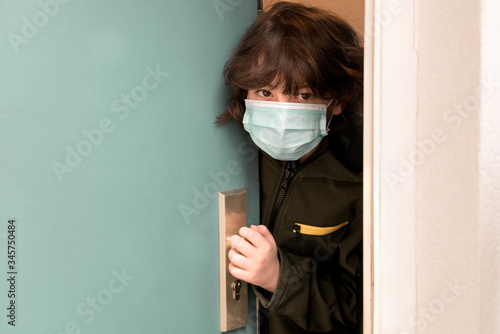A boy in a surgical mask looks out of the ajar door Wallpaper Mural