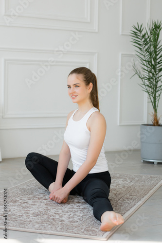 girl is engaged in stretching the hamstring, sitting in the apartment on the home carpet Tapéta, Fotótapéta