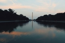 Washington Monument Amidst Silhouette Trees In Front Of Lake