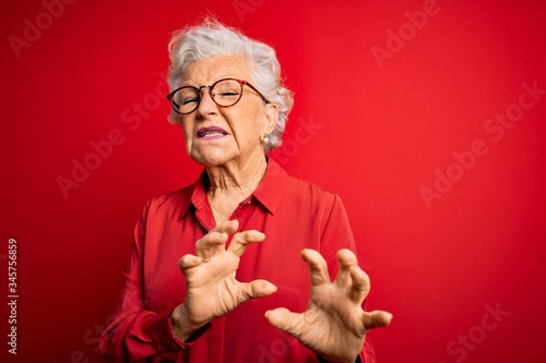 Senior beautiful grey-haired woman wearing casual shirt and glasses over red background disgusted expression, displeased and fearful doing disgust face because aversion reaction Canvas Print