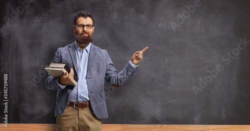 Obraz na plátně Male teacher holding books and pointing at a chalkboard