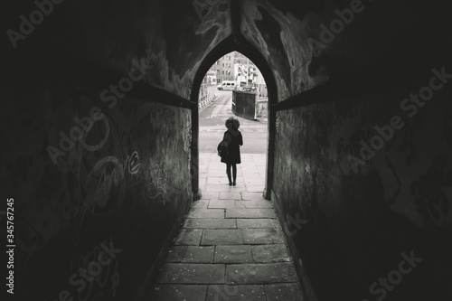 Photographie Rear View Of Woman Standing Outside Archway