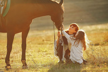 Mother And Daughter Next To Horse. Little Girl In A Summer Field. Family Playing With A Horse