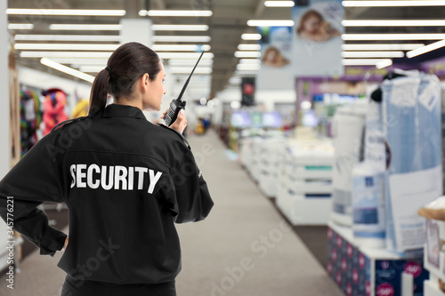Fotomural Security guard using portable radio transmitter in shopping mall, space for text