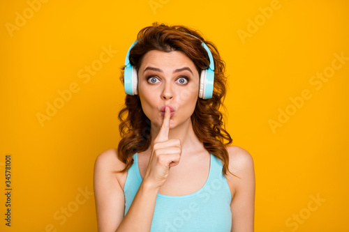 Fototapeta Shut up please. Photo of pretty funny lady listen modern technology youngster headphones favorite song hold finger on lips wear casual teal singlet isolated vibrant yellow color background obraz