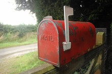 Close-up Of Old Red Mailbox On Fence