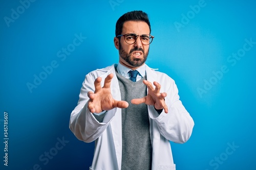 Young handsome doctor man with beard wearing coat and glasses over blue background disgusted expression, displeased and fearful doing disgust face because aversion reaction Canvas Print