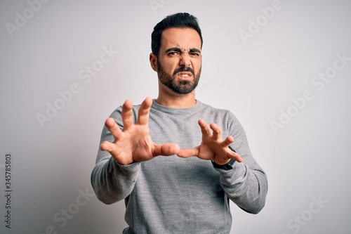 Photo Young handsome man with beard wearing casual sweater standing over white background disgusted expression, displeased and fearful doing disgust face because aversion reaction