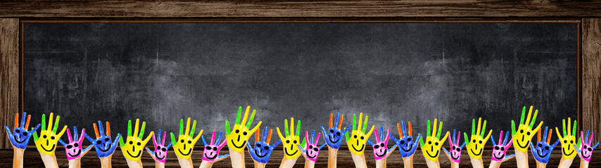 School background banner Panorama - Many brightly painted children's hands in front of a old aged empty blackboard with wooden frame and space for text
