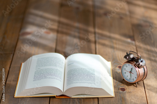 A hardback book opened for reading and a desk clock next to it Slika na platnu