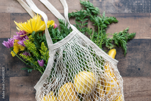 Fotografie, Obraz Closeup of reusable cotton knit bag with fresh flowers and produce