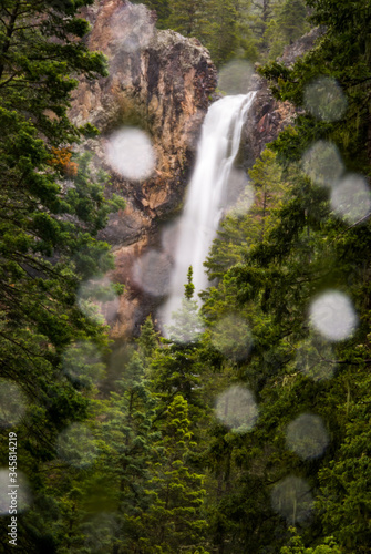 Waterfall through the rain in a deep green forest