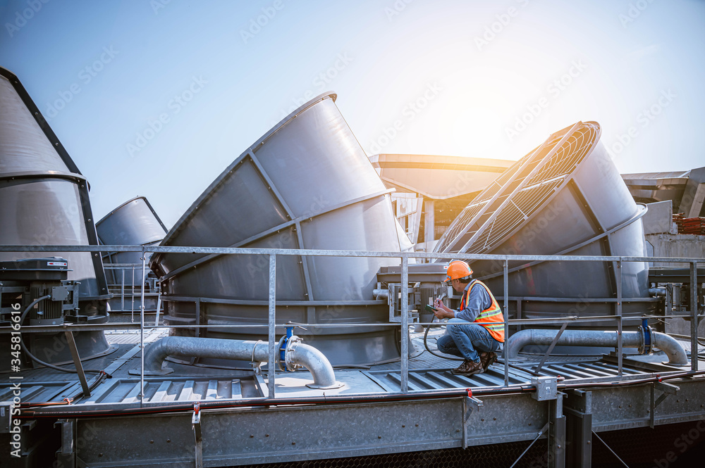 Fototapeta A engineer under checking the industry cooling tower air conditioner is water cooling tower air chiller HVAC of large industrial building to control air system.