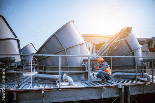 A engineer under checking the industry cooling tower air conditioner is water cooling tower air chiller HVAC of large industrial building to control air system Tableau sur Toile