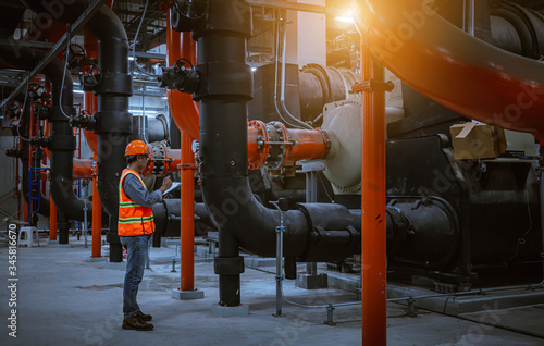Fototapeta A engineer under checking the industry cooling tower air conditioner is water cooling tower air chiller HVAC of large industrial building to control air system. obraz