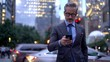 Mature male employer formally dressed walking in metropolitan downtown and typing text message for send via smartphone device, middle aged businessman using mobile device for phoning outdoors