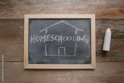 Valokuva Top view of a chalkboard written with Homeschooling on wooden background