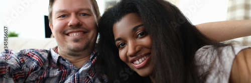 Leinwand Poster Portrait of cheerful mixed race couple taking happy selfie on sofa indoors