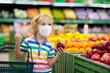 Leinwanddruck Bild - Child in supermarket. Kid grocery shopping.