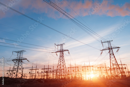 Electric network of pylons against a cloudy sky and a green meadow Fototapet
