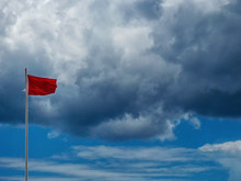 Low Angle View Of Red Warning Flag Waving Against Cloudy Sky