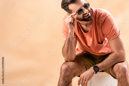 happy handsome man in shorts, summer t-shirt and sunglasses sitting on white cub Fototapete