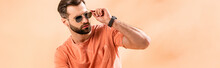 Panoramic Shot Of Stylish Young Man Posing In Shorts, Summer T-shirt And Sunglasses On Beige