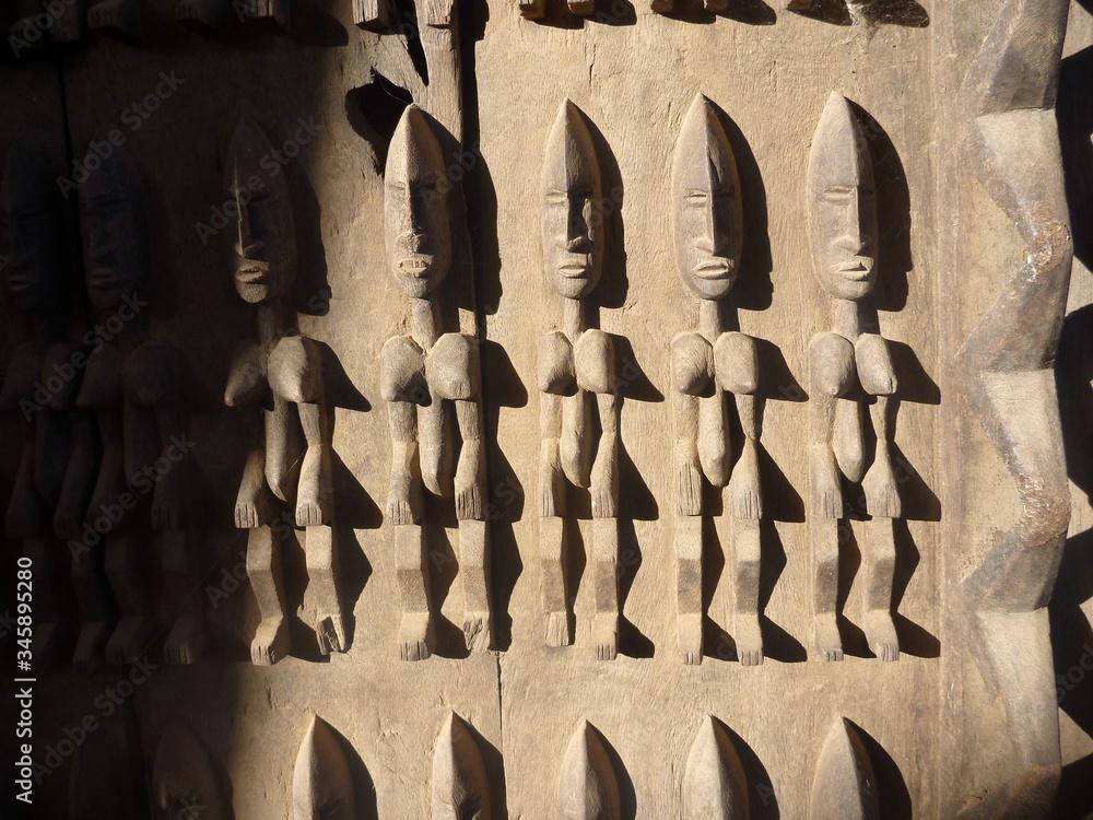 Fototapeta stara tradycyjna afrykańska płaskorzeźba na drewnianych drzwiach budynku w timbuktu przedstawiająca ludzkie postaci
