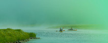 Few People On Kayaks Travel Across The Lake In A Misty Morning