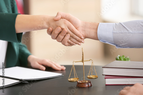 Photo Female judge and client shaking hands in office, closeup