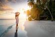 Eine attraktive Frau mit Hut steht am tropischen Strand unter Palmen auf den Malediven bei Sonnenuntergang