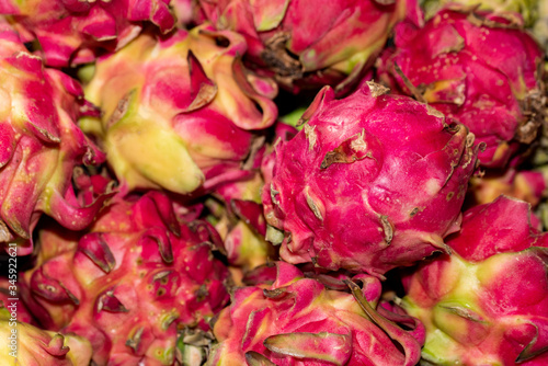 Valokuva Shriveled dragonfruit piled up in a market