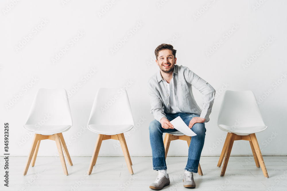 Fototapeta Smiling man with resume looking at camera while sitting on chair in office