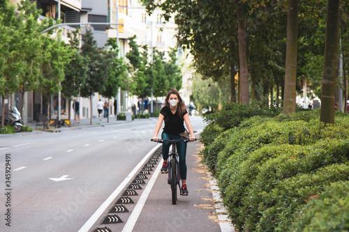 Chica joven de ojos claros, yendo en bicicleta durante coronavirus en una ciudad Canvas Print