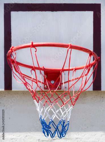 Photo New basketball hoop with red, white and blue net mounted on outdoor backboard