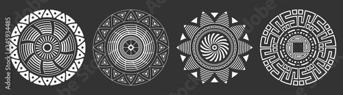 Fototapeta Set of four abstract circular ornaments. Decorative patterns isolated on black background. Tribal ethnic motifs. Stylized sun symbols. Stencil tattoo and prints Vector monochrome illustration. obraz