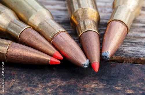 Carta da parati A close up of five different caliber rifle bullets together on a wooden backgrou
