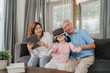 Asian grandparents and granddaughter using virtual reality and tablet play games at home. Senior Chinese, grandpa and grandma happy relax with young girl lying on sofa in living room concept.