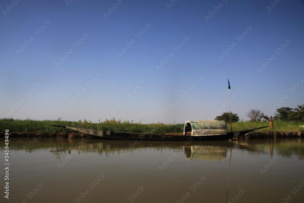 Fototapeta długie spiczaste czółno zacumowane przy trawiastym wybrzeżu spokojnej rzeki niger w afryce i czyste błękitne niebo