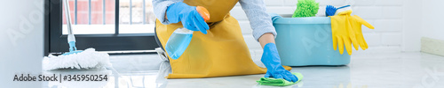 Fotografia Housekeeper maid wearing rubber gloves with cloth cleaning or applying floor care and cleaners at home, housework and housekeeping concept
