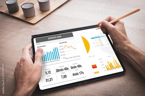Leinwand Poster Tablette numérique tenue en main par un homme au travail avec une présentation d