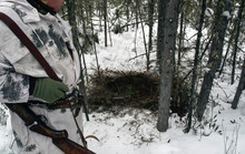 Hunter In White Winter Camouflage With A Weapon At The Riding Den Of A Siberian Bear Or Grizzly.