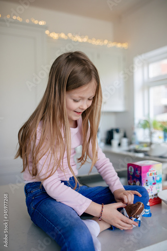 little girl unwrapping chocolate easter egg Canvas-taulu