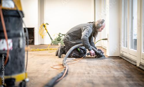 Fotografie, Obraz Handwerker schleift den Parkettboden mit dem Randschleifer